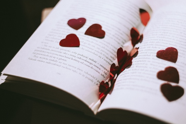a book with small cut-out heart glitter | advocating-for-romance-books-share-the-love on valentines day reading | BL | Black Lion Journal | Black Lion